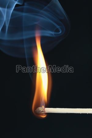 entzuendetes streichholz mit blauem rauch auf