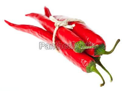 buendel von chilis auf weissem hintergrund
