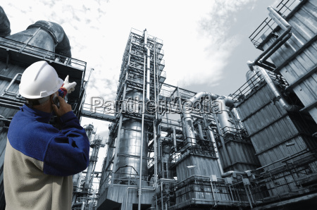 engineer pointing at oil refinery