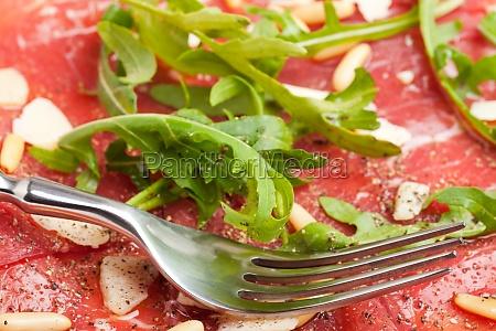 carpaccio auf einem teller mit parmesan