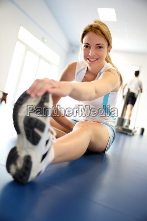 woman stretching out in gym center