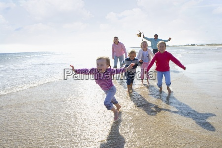 young happy family running on beach