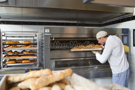 baker checking tray of bread in