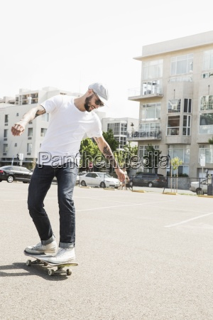 young man skateboarding in a car