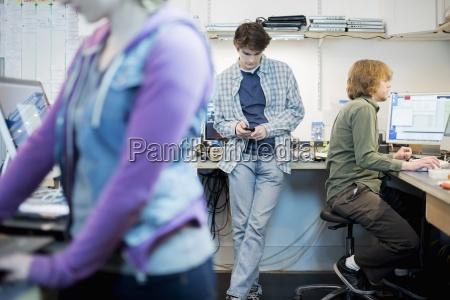 three people at a computer repair