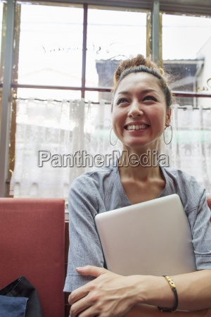 a woman holding a laptop in