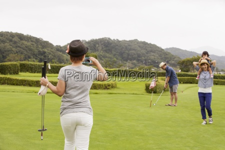 family on a golf coursea child