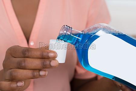 person pouring mouthwash into bottle cap
