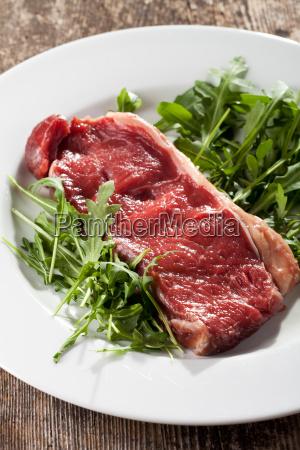 rohes steak auf rucolasalat