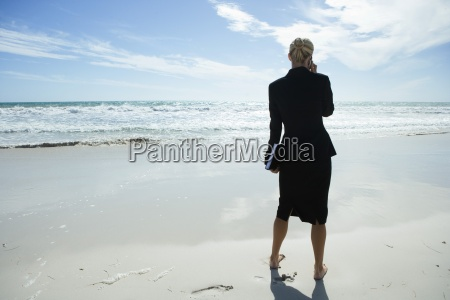 businesswoman using cell phone standing on