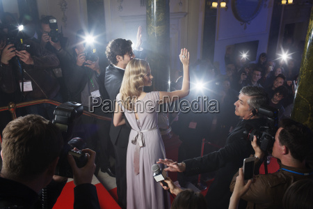 celebrity couple waving to fans and