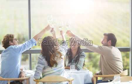 friends toasting wine glasses overhead at