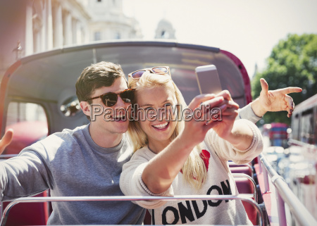 couple taking selfie on double decker