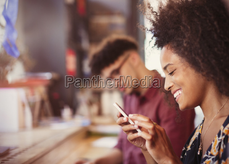 smiling woman texting with cell phone