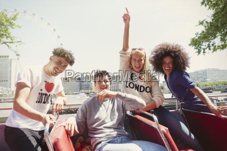 portrait enthusiastic friends riding double decker