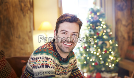 man sitting on couch by christmas
