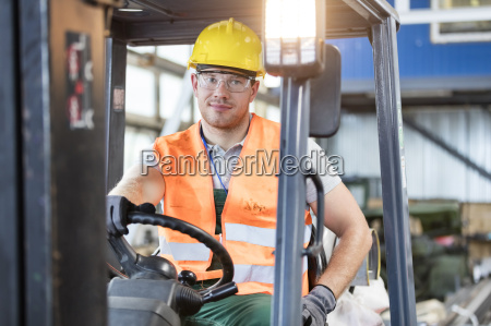 portrait worker driving forklift in factory
