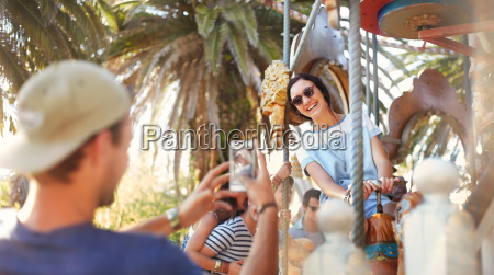 young man photographing woman on carousel