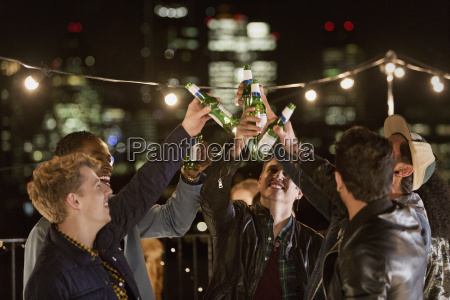 young men toasting beer bottles at