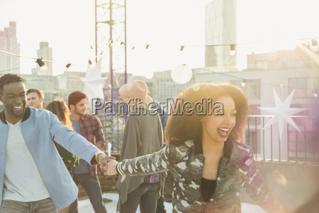 playful young couple at rooftop party