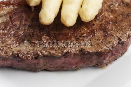 weisser spargel auf einem steak