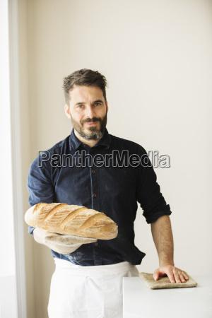 baker holding two freshly baked loaves