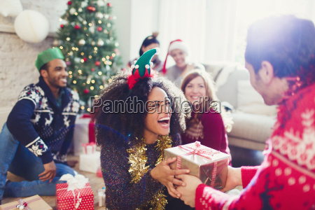 enthusiastic friends exchanging christmas gifts