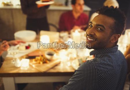 portrait smiling man enjoying candlelight christmas