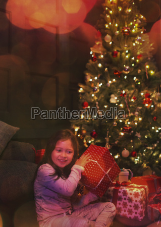 curious girl shaking gift at christmas