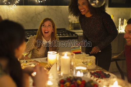 laughing friends enjoying cake at candlelight