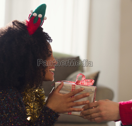 enthusiastic girlfriend receiving christmas gift from