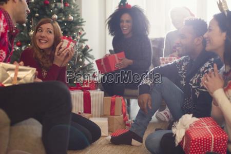 friends watching playful woman shaking christmas