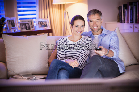 smiling couple watching tv in living