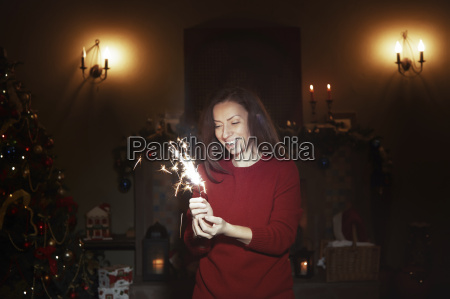 smiling woman with sparkler firework in