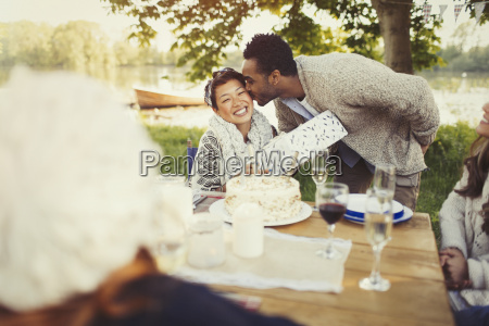 boyfriend kissing girlfriend with birthday gift