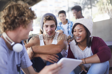 teenage friends hanging out using digital