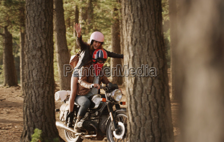 exuberant young woman riding motorcycle in