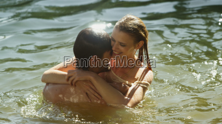affectionate couple hugging and swimming in