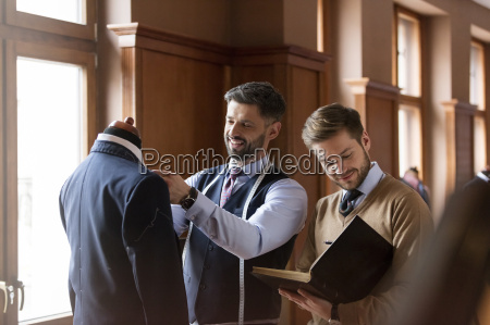 tailors examining suit and taking notes