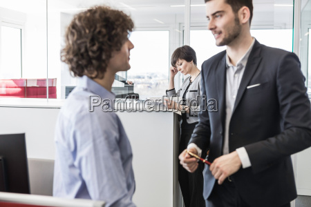businessmen having conversation in office woman
