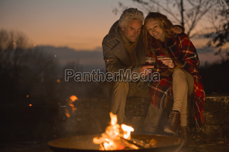 couple drinking enjoying autumn campfire