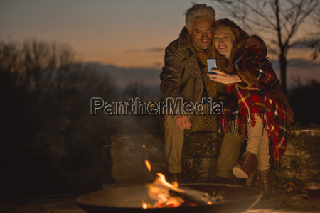 couple using cell phone at autumn