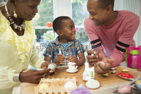 multi generation family decorating easter eggs