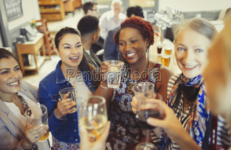 women friends toasting wine and beer