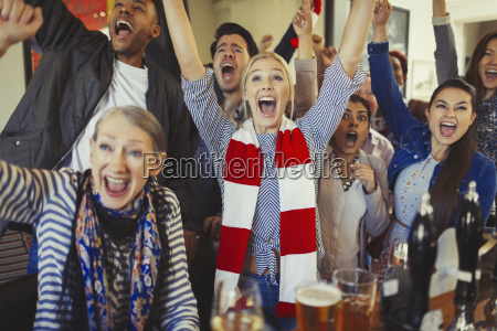 enthusiastic sports fans cheering watching game