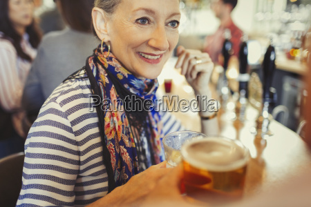 senior woman drinking beer at bar