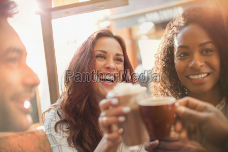 enthusiastic friends toasting coffee cups at