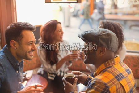 friends talking and drinking coffee in