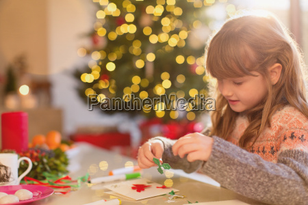 girl making christmas decorations at table