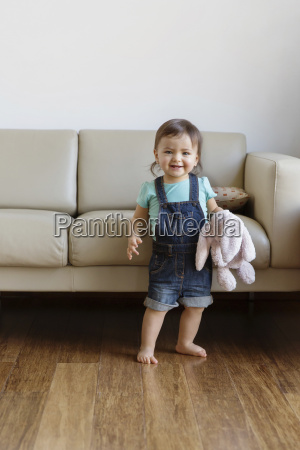 smiling young boy wearing denim dungarees